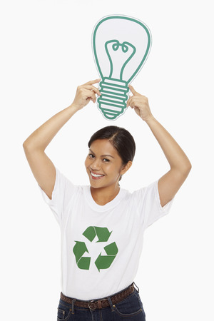 Happy woman holding up a cardboard light bulb Stock Photo - 22840890
