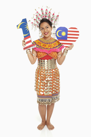 Woman in traditional clothing holding up a number one shape and a heart shape photo