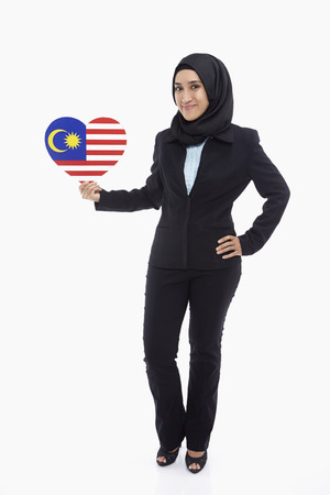 Businesswoman holding up a heart shaped Malaysian flag photo