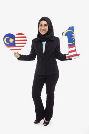 Businesswoman holding up a heart shape and a number one shape photo