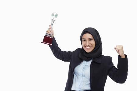 Businesswoman with a winning trophy, smiling and cheering photo