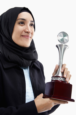 Businesswoman with a winning trophy, smiling photo