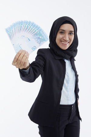 malay ethnicity: Businesswoman holding up cash