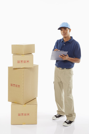 person writing: Delivery person writing notes on clipboard Stock Photo