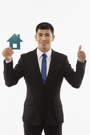 Businessman holding up a cut out house, giving thumbs up photo