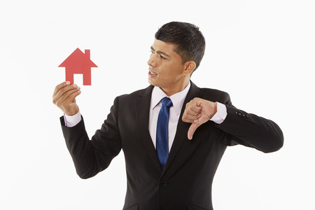 Businessman holding up a cut out house, giving thumbs down photo