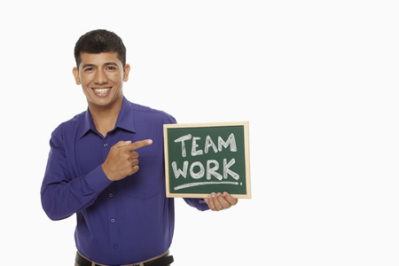 Businessman holding up a blackboard with Team work written on it photo