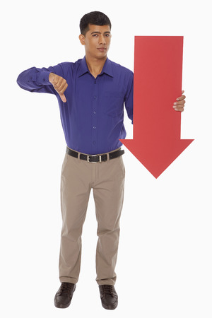Businessman holding up a red arrow, with thumbs down photo