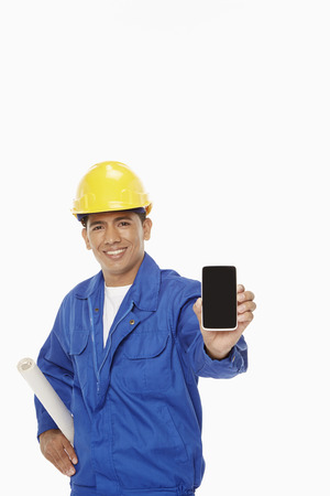 Construction worker holding up a mobile phone photo