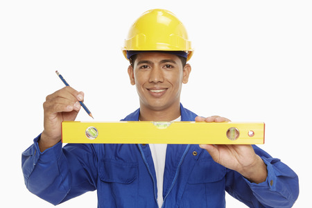 spirit level: Construction worker measuring with a spirit level