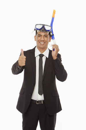 Businessman with swimming gear giving thumbs up photo