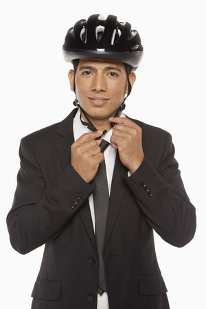 Businessman putting on a bicycle helmet photo