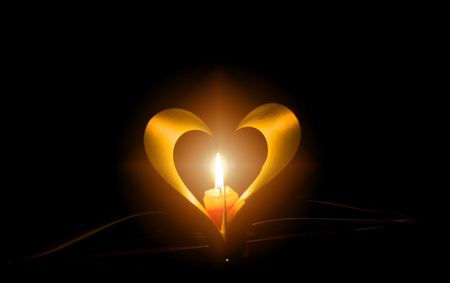 Light a candle in the night. Shining through the book fold up the lighting concept of knowledge and love.