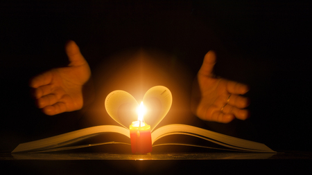 Light a candle in the night. Placed near the book fold up are heart-shaped and hand submissions lighting concept, knowledge and love.