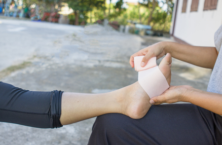 Volunteers are provided to patient ankle wrap Elastic Bandage, with patient ankle injury. Imagens