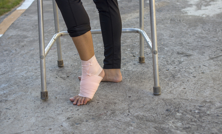 Volunteers are provided to patientankle wrap Elastic Bandage, with patient ankle injury. use walker frame.
