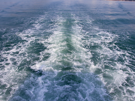 Bright green and blue sea water, wallpaper or background. The waves caused by the ship. 版權商用圖片