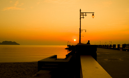Silhouette of a seaside Pier in the morning sun and sky gold. Standard-Bild
