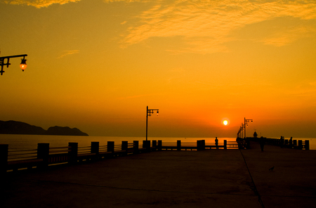 Silhouette of a seaside Pier in the morning sun and sky gold. Standard-Bild - 121328332