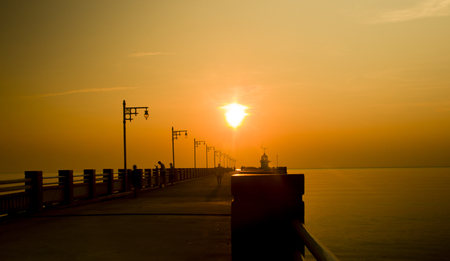 Silhouette of a seaside Pier in the morning sun and sky gold. Standard-Bild - 121328334