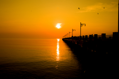 Silhouette of a seaside Pier in the morning sun and sky gold. 스톡 콘텐츠