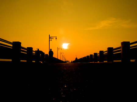 Silhouette of a seaside Pier in the morning sun and sky gold. Standard-Bild - 121328336