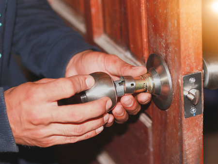 En el enfoque selectivo en el pestillo de los viejos técnicos de reparación de pestillos de la puerta del baño, mediante la sustitución de los pernos defectuosos. Foto de archivo
