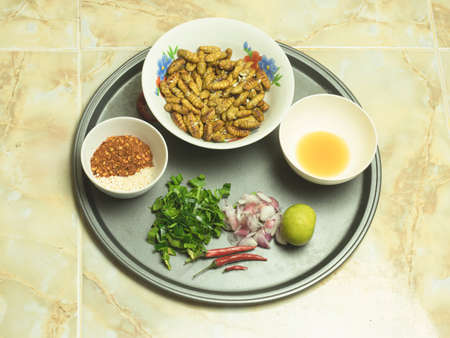 Pupa salad of silkworms, a popular food eaten in the northeastern part of Thailand. The garnish consists of lemons, dill, onion, cayenne pepper, fresh chillies. Banque d'images - 151920256
