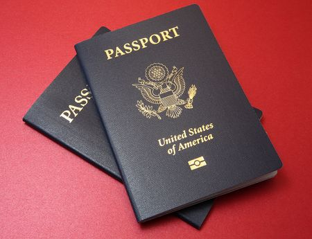 Two blue United States passports arranged on a fine textured red background material Standard-Bild