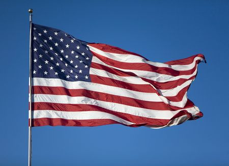 flagpoles: Very large United States Flag blowing in the wind on a cloudless day