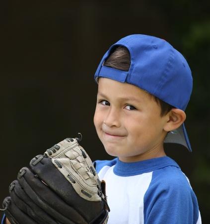 Chico de béisbol hispano con ropa azul y blanca y guante sobre fondo oscuro