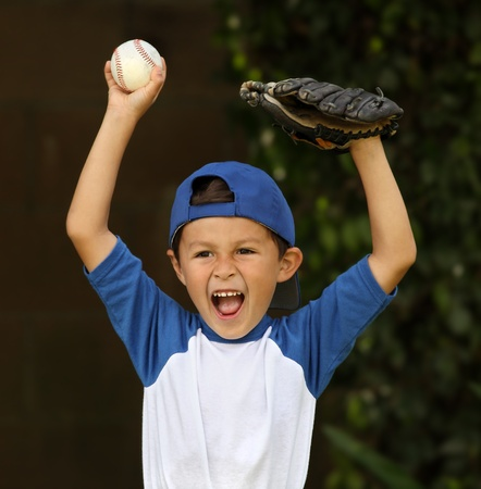 Young hispanic boy with baseball and glove celebrates on dark background Stock Photo