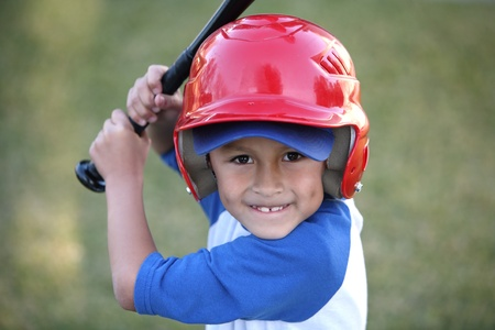 Young hispanic or latino boy with red baseball helmet over a blue hat and ble tee shirt.