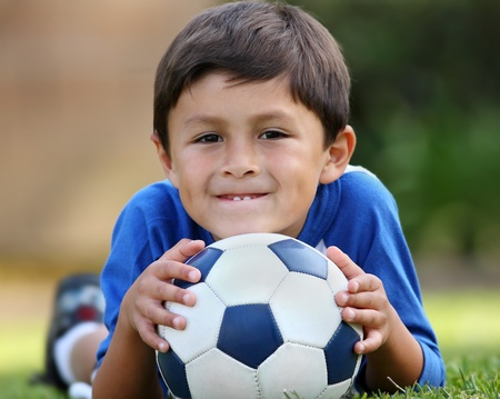 ballon foot: Young brown haired hispanic boy in blue shirt lying down on grass with soccer ball in hands