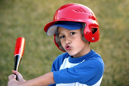 Young hispanic or latino boy with red baseball helmet over a blue hat and ble tee shirt. photo