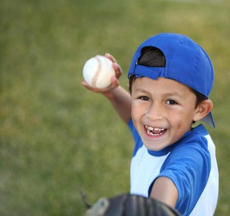 Feliz sonriente latino joven vestido con mangas de béisbol azul con tapa, guante y pelota Foto de archivo