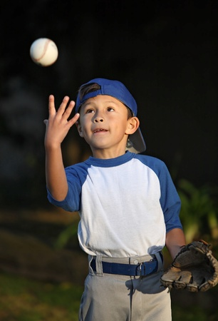Happy smiling young latino boy dressed in blue baseball sleeves with cap, glove and ball Stock Photo - 9837865