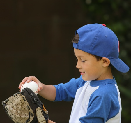 Young cute hispanic boy playing with baseball and glove wearing blue hat on dark background photo