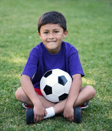 Authentic young Latino boy sitting cross-legged with soccer ball on field of grass Standard-Bild
