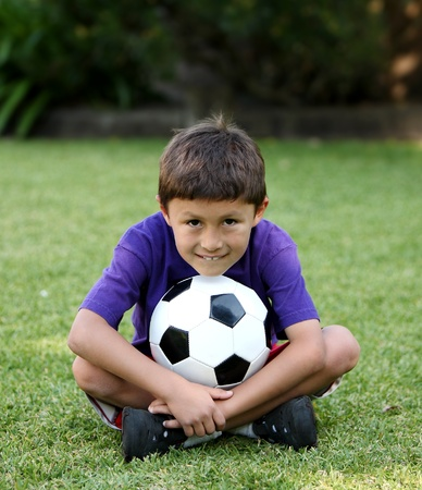 Young Latino boy sitting ion grass with soccer ball Stock Photo