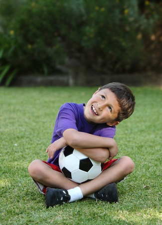 Happy boy with soccer ball sitting on grass Stock Photo