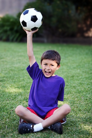 Young boy holds up soccer ball while sitting on grass