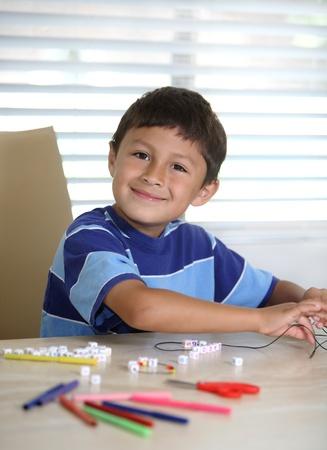 Happy Hispanic or Latino boy playing at crafts
