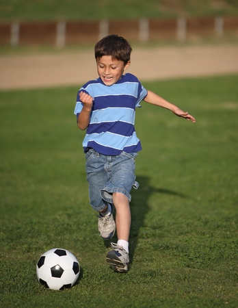 Authentic happy Latino boy playing with soccer ball in field wearing blue striped tee shirt. Stock Photo