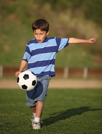 kids activities: Authentic happy Latino boy playing with soccer ball in field wearing blue striped tee shirt. Stock Photo