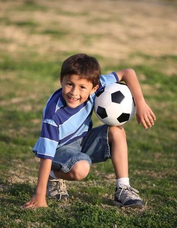 ni�os latinos: Aut�ntico ni�o hispano feliz jugando con el bal�n de f�tbol en el campo de color azul camiseta de rayas.