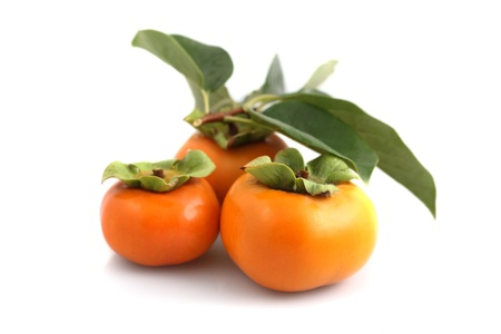 persimmons: Organic persimmons in a group on white background