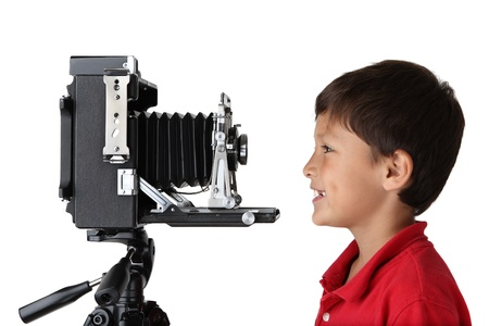 Happy smiling boy in red shirt looking into old press camera on white background Stock Photo