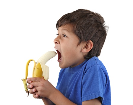 Young boy prepares to bite banana - on white background