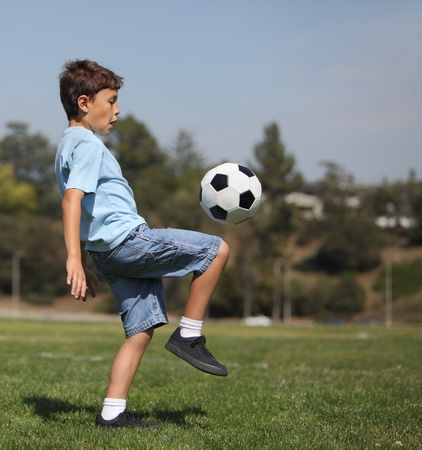 A young boy knee kicks a soccer ball in a park with copy space to right photo